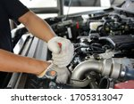 Small photo of Automotive mechanic working in garage. Repair service. Mechanic working on a diesel engine, close up. Technician hands of car mechanic in doing auto repair service and maintenance worker repairing.