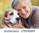 Stock photo senior woman hugs her beagle dog in countryside 170540894