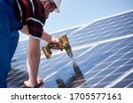 Small photo of Male engineer in protective helmet installing solar photovoltaic panel system using screwdriver. Electrician mounting blue solar module on roof of modern house. Alternative energy ecological concept.