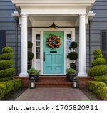Small photo of Beautifully decorated turquoise colored front door of traditional home. Brick path and trimmed hedges.