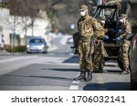 Small photo of Military soldier controls on the street. Security patrol with masks and gloves monitor passing motorists. Daily street control for the Covid-19 global crisis. The army at work in the streets of Europe