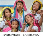 Small photo of LOIKAW, KAYAH STATE / MYANMAR (BURMA) - MARCH 27, 2019: Five boisterous Myanmarese Kayan Lahwi girls with polished tribal brass neck rings pull faces for the camera, on March 27, 2019.