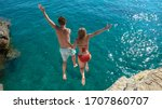 Small photo of Joyful tourist couple decides to jump off a rocky cliff and dive into sea. Unrecognizable man holds his gorgeous girlfriend's hand while diving into the refreshing blue sea on a sunny summer day.