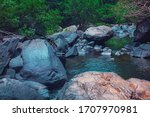 Strong flood of water rocks below.Crystal clear water, huge stones with a beautiful vegetation around. At the end forming a strong current and later a calm lake with clean transparent in India - stock photo