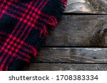 Small photo of Plaid blanket overtop old wood planks