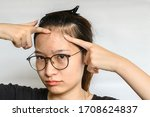 Small photo of Portrait of woman trying to pointing problem of Acne and Scar from acne inflammation (Papule and Pustule) on her forehead. Conceptual of problems on woman skin.