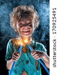Portrait of little crazy electrician over black background - stock photo