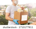 Small photo of Coronavirus Donation box. Delivery food. Volunteer. Food help. A man in a mask and medical gloves holds a box of food on the street. Coronavirus volunteer. Quarantine