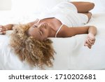 Small photo of A young woman relaxing on her bed