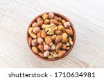 A Mixture Of Nuts In A Clay...