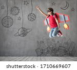 Happy child playing with toy paper wings. Kid pilot having fun at home. Success, innovation and space concept