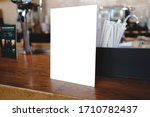 Small photo of Mock up Menu frame in shopping mall,Stand for booklets with white sheets of paper acrylic tent card on table on.
