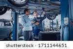 Small photo of Manager Checks Data on a Tablet Computer and Explains the Breakdown to a Mechanic. Car Service Employees Inspect the Bottom and Skid Plates of the Car. Modern Clean Workshop.