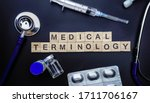 Small photo of MEDICAL TERMINOLOGY wooden word against black background with stethoscope, syringe, vial and pills. Medical Concept