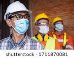 Industrial engineering team wears a COVID 19 protective mask. Workers wear a quarantine mask to prevent the spread of Covid 19 by wearing a face mask. Coronavirus disease. - stock photo