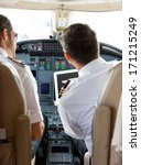 Small photo of Rear view of pilot and copilot using digital tablet in cockpit of private jet