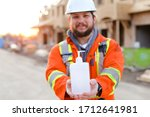 Focus on disinfectant soap given by engineer wearing orange workwear and hardhat at construction site. Concept of corona virus protection and disinfectant for washing hands. - stock photo