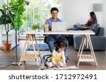 Small photo of Mixed race family sharing time in living room. Caucasian father using notebook computer to work and half-Thai playing and painting under desk while Asian mother with laptop working her job on sofa.