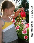 Young girl watering flowers - stock photo