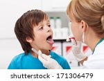 Boy at the doctor - a healthcare professional taking biological samples for testing - stock photo