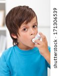 Boy using inhaler for respiratory system issues - stock photo