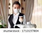 Small photo of A female Waiter of European appearance in a medical mask serves Latte coffee
