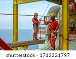 Working at height. A group of abseilers wearing red coverall and Personal Protective Equipment (PPE) standing on the piepeline managing their rope access with background open sea. - stock photo