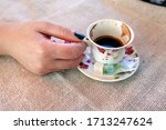 Woman hand holding traditional porcelain Turkish coffee cup. Turkish coffee cup & Turkish delight. - stock photo