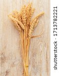 Small photo of Bunch of wheat ears on wooden table. Sheaf of wheat on vintage background.