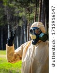 Small photo of Life after age of coronaviruses. Man in protective suit, ABC-protective mask (box respirator) takes walk in spring forest. How will life change after Covid-19 - changing social paradigm concept