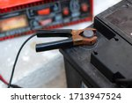 Close up of a car battery jumper cable with black minus copper clamps attached to the auto battery. Battery charger in background. - stock photo