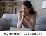 Small photo of Nervous young woman sitting on sofa, worrying about bad news, received by email on laptop. Stressed businesswoman thinking of crisis challenges, feeling desperate or unsure, stack with hard decision.