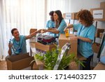 Small photo of Active people enjoys volunteering at food bank. Voluntary company. Curly beautiful girl working in voluntary company with friends putting food for donation into boxes.