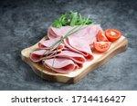 Fresh pork ham slices on cutting board over dark background