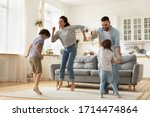Small photo of Full length overjoyed family of four jumping to music in modern studio living room. Excited young married couple dancing with playful little children siblings, spending active free time at home.