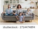 Small photo of Full length peaceful calm couple practicing yoga exercises with small children in studio living room. Mindful little boy sitting on floor in lotus pose while parents relaxing on sofa with sister.