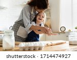 Small photo of Smiling mother having fun with small preschool kid daughter, playing with dough in kitchen. Happy adorable little child girl in apron enjoying cooking homemade pastry together with mommy at home.