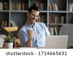 Small photo of Excited man wearing glasses celebrating success, reading good news in email, happy overjoyed businessman looking at laptop screen, showing yes gesture and laughing, sitting at work desk