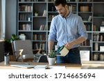 Confident businessman wearing glasses watering plant on work desk, serious focused man holding plastic pot with water, standing near table in modern office cabinet, new startup project - stock photo