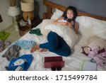 Small photo of slackness and disorganized during covid-19 home lockdown - young disorderly and chaotic Asian Chinese woman on bed using internet mobile phone on grimy messy bedroom in social media addiction
