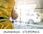 Men in Yellow Biochemical Hazmat Suite and Breathe Protection Mask Looking Outside the Window. Industrial Theme. - stock photo