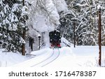 Small photo of Steam train ride in winter forest snow. Locomotive steam train ride in winter forest. Winter forest steam train ride