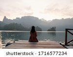 Small photo of An Asian woman wearing a hijab watching the sunrise in the morning on a floating raft Sneak around with rivers and mountains Sai Chon Dam, Ratchaprapa Dam and Cheow Lan Dam, Khao Sok, Surat Thani