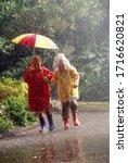 Children In Raincoats Sharing...