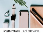 Small photo of Pink and blue flat lay home office with modern gadgets such as smartphone, smartwatch, earphones, notepad, pen. Pink and blue colors. Copyspace to write. Minimalist style to enhance productivity