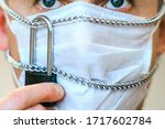 Small photo of The concept of primary protection against the spread of coronavirus. The mask on the face of the man that was chained and padlocked. Be sure to wear the mask yourself and insist that your neighbors