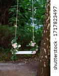 Small photo of Wooden swing in playground outdoors. Empty swing placed in park. Wedding swing decorated with flowers roses. Garden swing hanging from a large tree on green grass background. Garden decor. Romance
