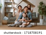 Small photo of Mother, father and children girls in the room with a symbol of roof. Concept of housing for young family.