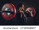 asian athletic strong man having workout and bodybuilding with barbells weightlifting front squat style in gym and fitness center in dark tone, selective focused - stock photo