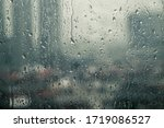 Small photo of Closeup raindrops water droplets trickling down on wet clear window glass during heavy rain against blurred city view in rainy day monsoon season